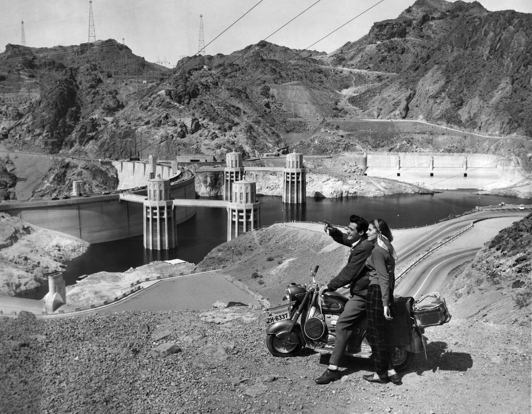 The mighty Hoover Dam impresses a young Swiss couple making their first tour of United States on their scooter, April 9, 1954 in Nevada. Natives of Zurich, Fred and Beatrice Troller were veteran s ...