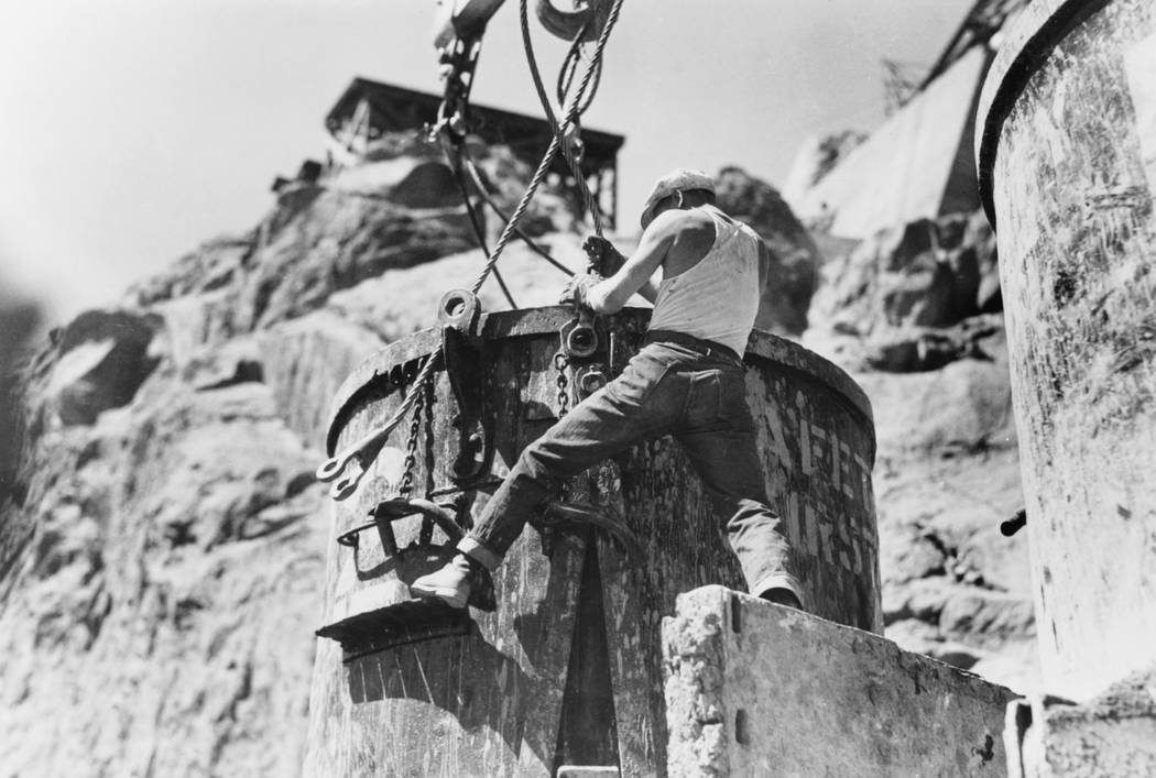 A Workman attaches cables to an eight cubic yard capacity concrete bucket at a transfer station on the Nevada rim of Black Canyon during Hoover Dam construction in Sept. 1934. (Library of Congress )