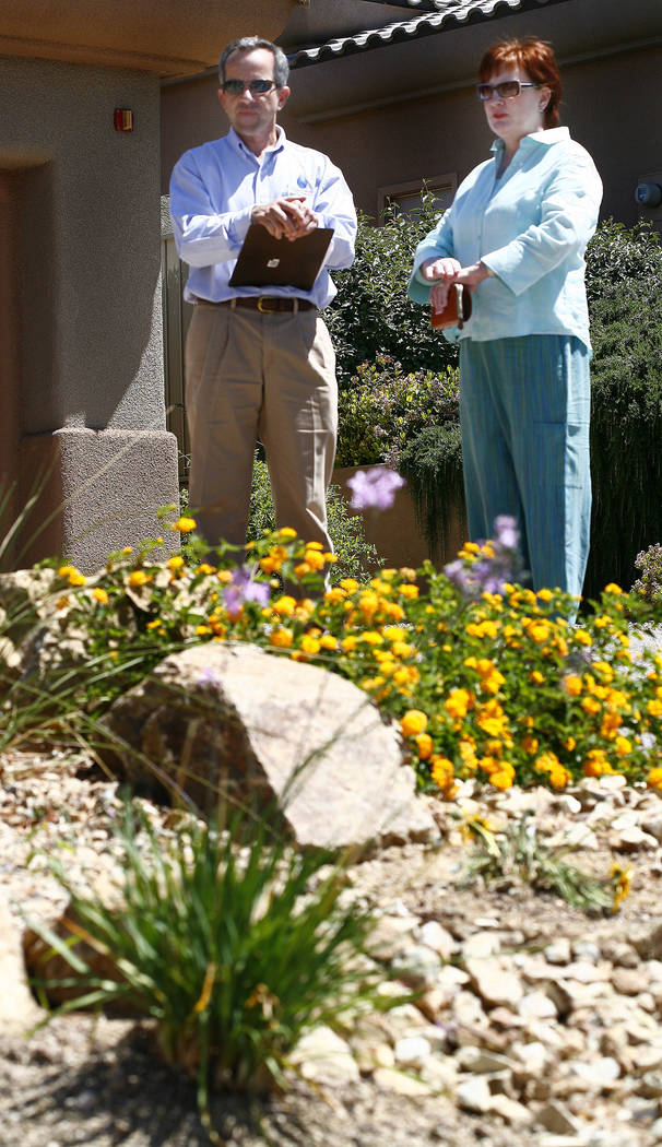 Southern Nevada Water Authority Conservation Manager Doug Bennett (left) looks over the front yard landscaping of homeowner Kathy Gillespie in May 2008. (Review-Journal file)
