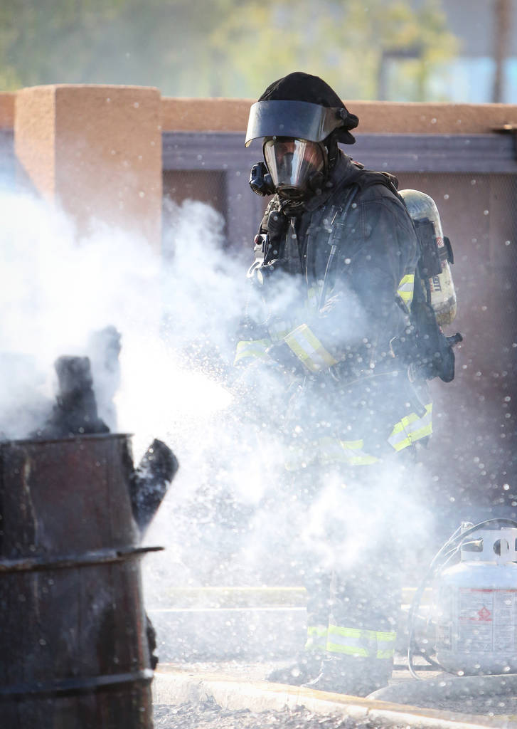 North Las Vegas firefighter Darcy Loewen hoses down a smoking barrel of wood during a training session at North Las Vegas Fire station 52 in Las Vegas, Tuesday, Dec. 18, 2018. Caroline Brehman/Las ...