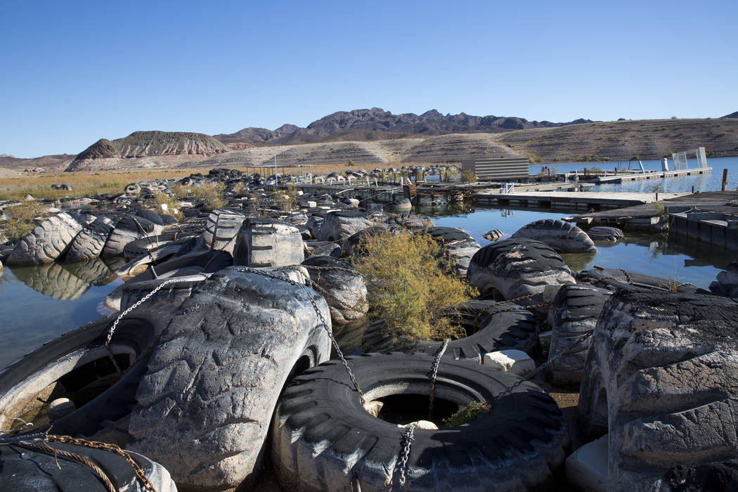 Rows of tires once used to control the wake and several defunct boating docks are seen pushed up against a shoreline just north of the Callville Bay Resort & Marina at Lake Mead National Recre ...