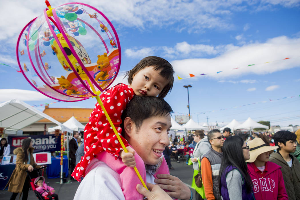 Matt Chen holds his daughter Allie, 3, on his shoulders while they watch a traditional lion dance preformed by the Lohan school of Shaolin during the 23rd annual Chinese New Year Celebration and A ...