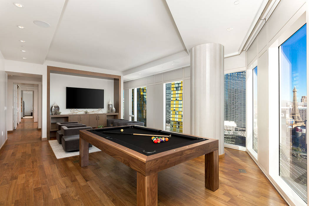 The living room in Waldorf Astoria unit No. 2403 has a game area. (Luxury Estates International)