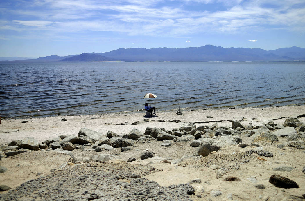 FILE - In this April 30, 2015 file photo, a man fishes for tilapia along the receding banks of the Salton Sea near Bombay Beach, Calif. Work on a multistate plan to address drought on the Colorado ...