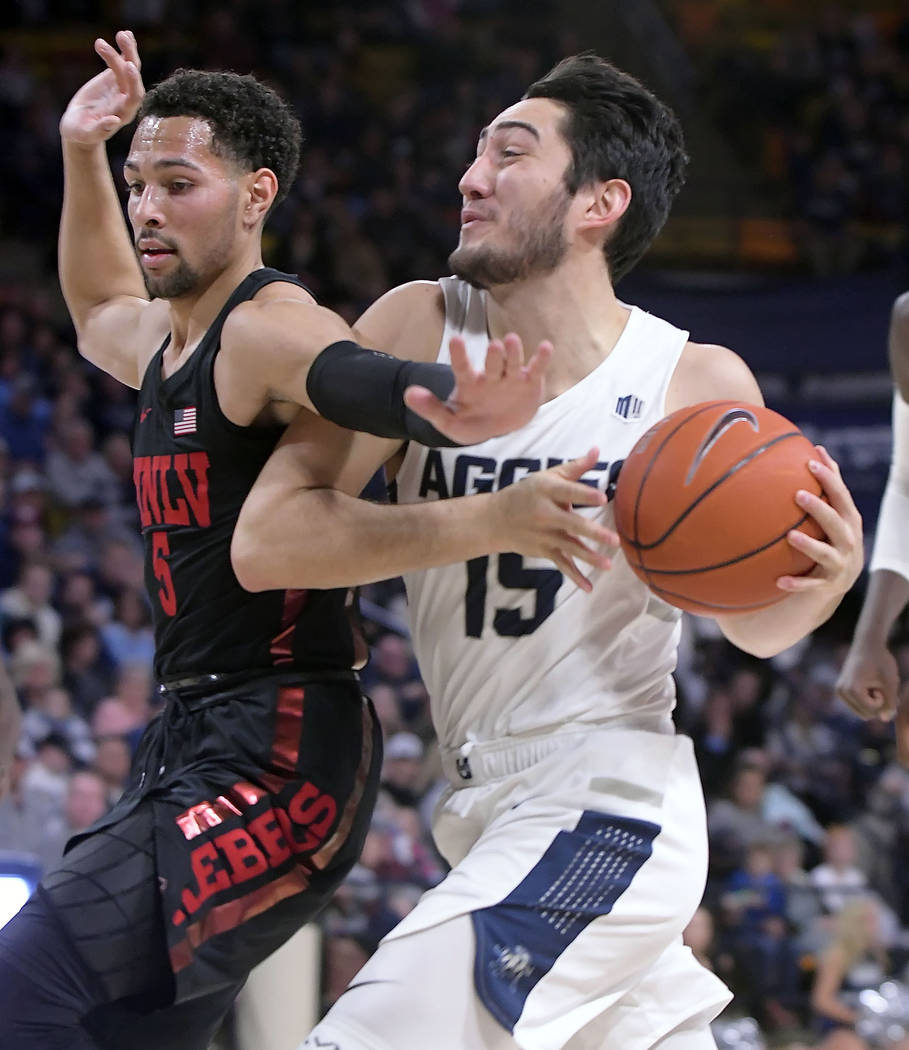 Utah State guard Abel Porter (15) gets fouled by UNLV guard Noah Robotham (5) during an NCAA college basketball game Saturday, Feb. 2, 2019, in Logan, Utah. (Eli Lucero/The Herald Journal via AP)