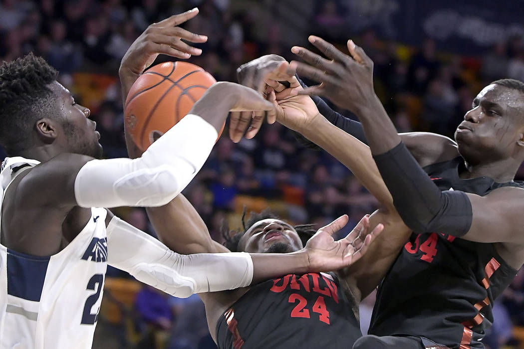 Utah State center Neemias Queta, left, fights for a rebound against UNLV forwards Joel Ntambwe (24) and Cheikh Mbacke Diong (34) during an NCAA college basketball game Saturday, Feb. 2, 2019, in ...