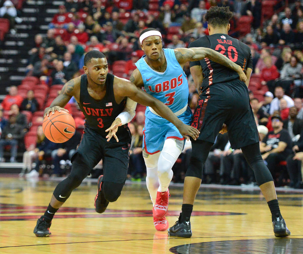 UNLV Rebels guard Amauri Hardy (3) uses forward Nick Blair (20) to get past New Mexico Lobos guard Keith McGee (3) during the second half of the UNLV Rebels and the New Mexico Lobos NCAA basketbal ...