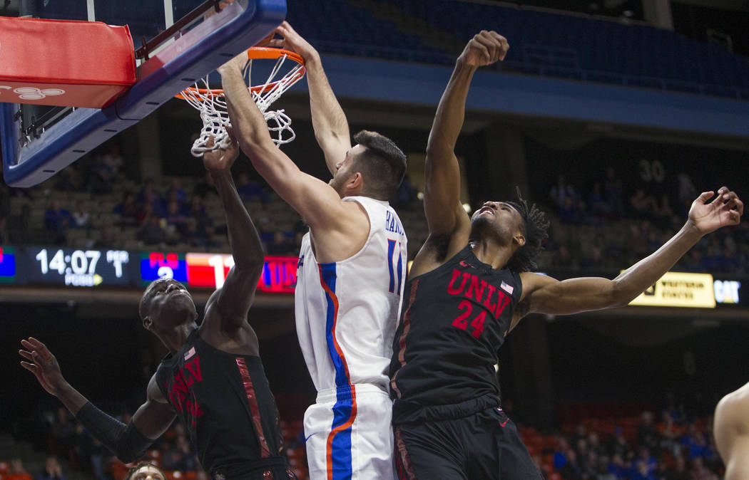 Boise State forward Zach Haney attempts a dunk but is fouled by UNLV forward Joel Ntambwe with UNLV's Cheikh Mbacke Diong also on the play during an NCAA college basketball game Wednesday, Feb. 6, ...