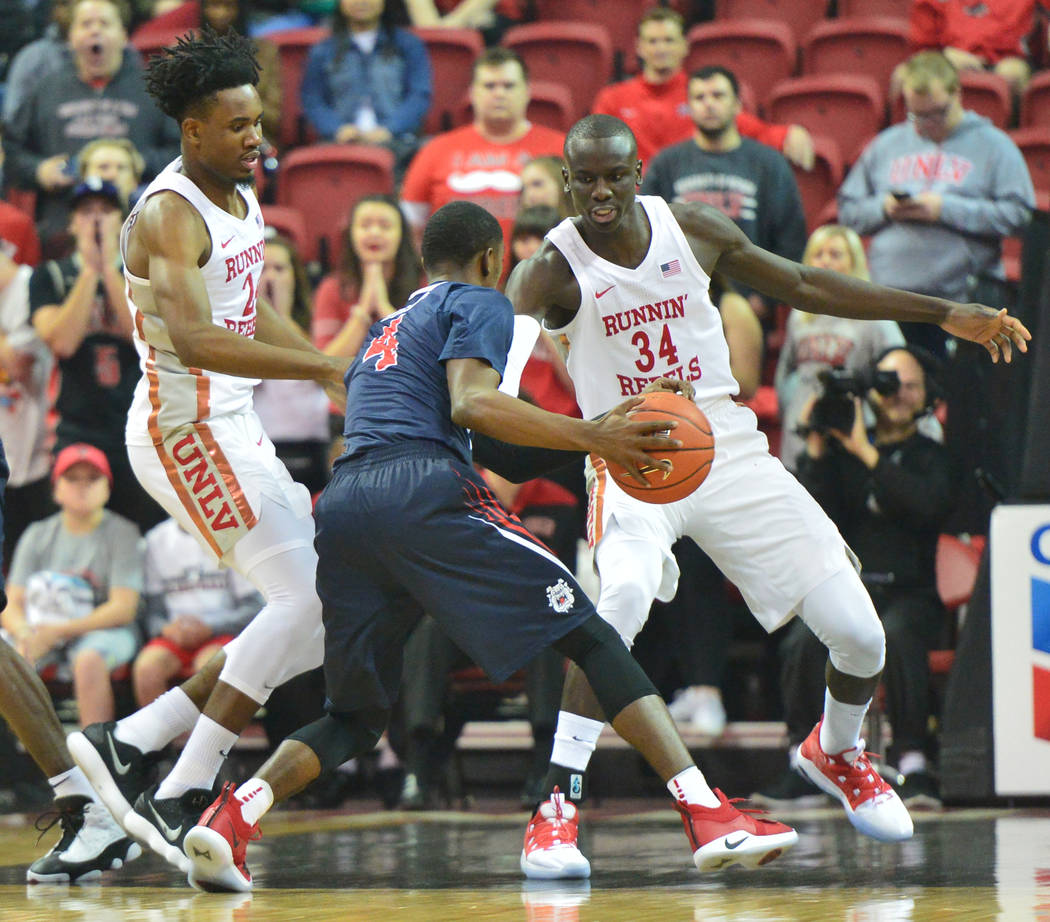Fresno State Bulldogs guard Braxton Huggins (4) is double teamed by UNLV Rebels forward Joel Ntambwe (24) and forward Cheikh Mbacke Diong (34) during the first half of a game between UNLV and Fres ...