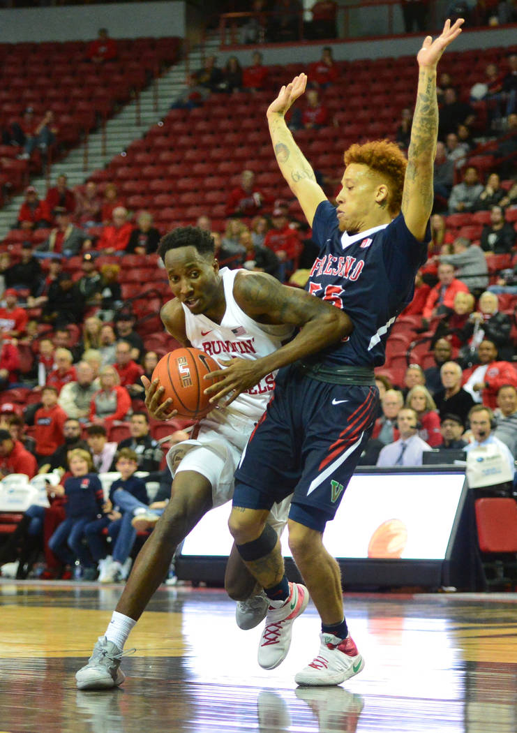 UNLV Rebels guard Kris Clyburn (1) finds a way around Fresno State Bulldogs guard Noah Blackwell (55) during the second half of a game between UNLV and Fresno State at the Thomas & Mack Center ...