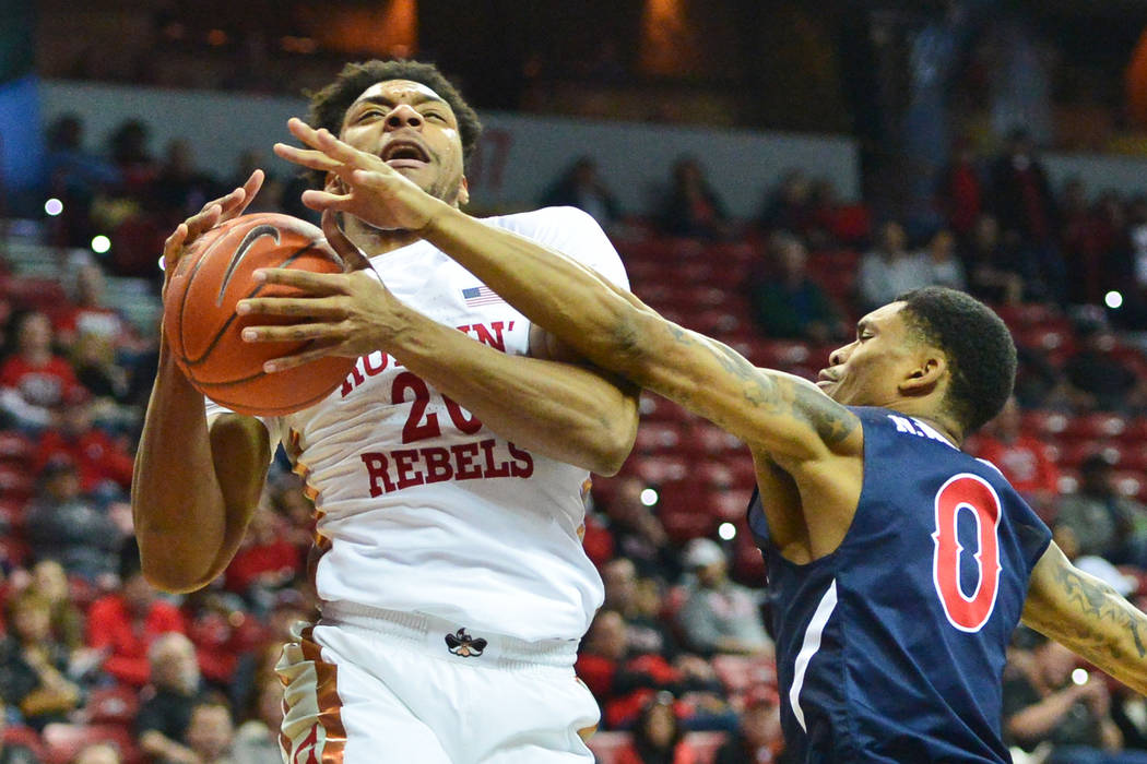 UNLV Rebels forward Nick Blair (20) goes up for a shot against Fresno State Bulldogs guard New Williams (0) only to get called for traveling during the first half of a game between UNLV and Fresno ...