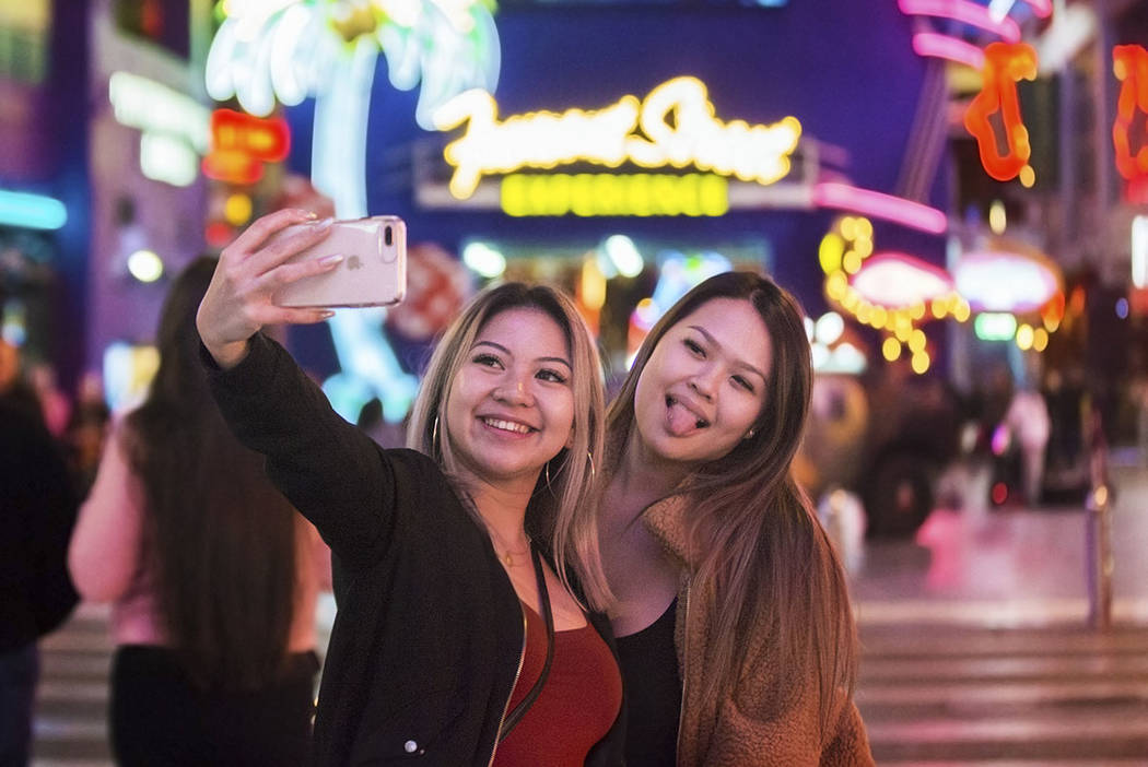 Camile Sangalang, left, and Jasmine Hsiao, both from Vancouver, British Columbia, take a selfie in front of the Fremont Street Experience sign on Wednesday, Jan. 30, 2019, in Las Vegas. (Benjamin ...