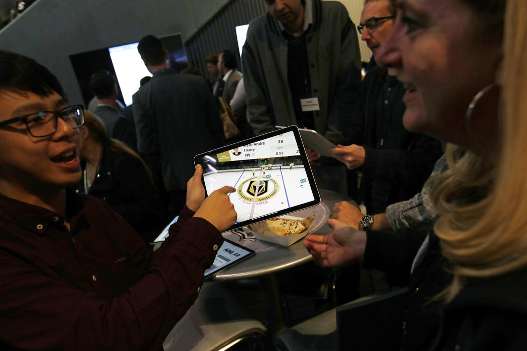 People watch real-time puck and player tracking technology on a tablet during an NHL hockey game between the Vegas Golden Knights and the San Jose Sharks in Las Vegas, Thursday, jan. 10, 2019. The ...
