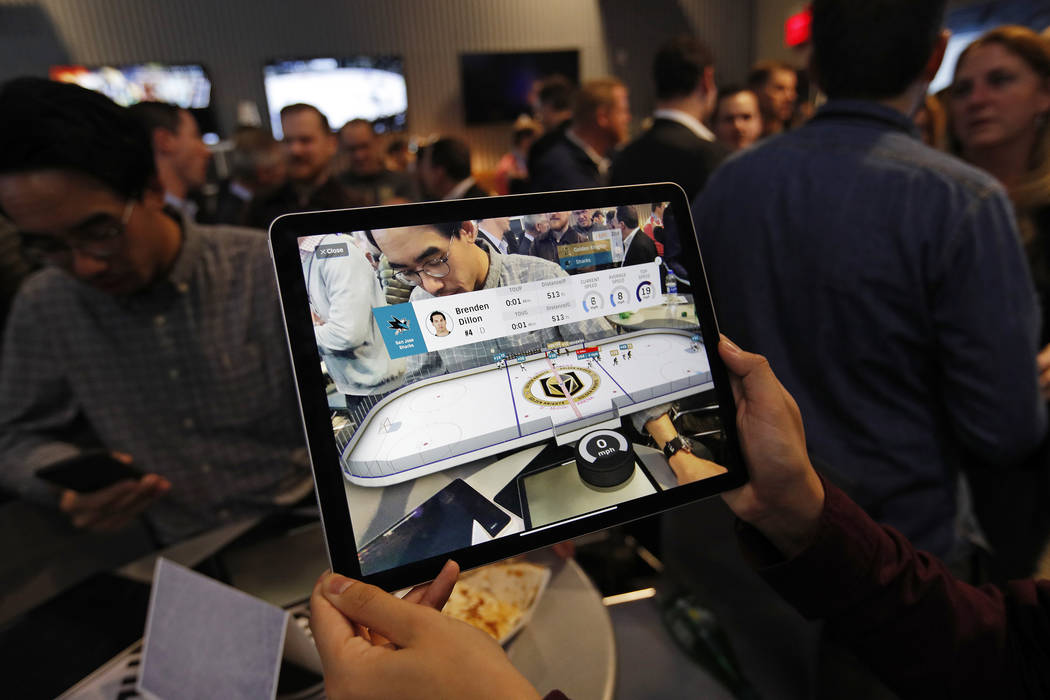 People watch real-time puck and player tracking technology on display during an NHL hockey game between the Vegas Golden Knights and the San Jose Sharks in Las Vegas, Thursday, Jan. 9, 2010. The N ...