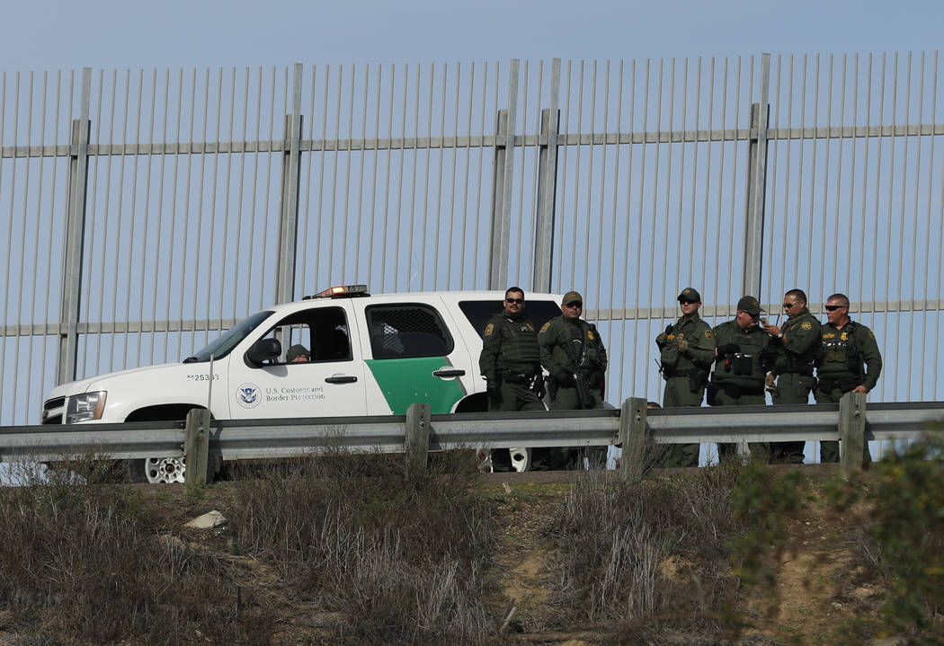 U.S. Border Patrol agents stand in front of a secondary fence in San Diego. (AP Photo/Rebecca Blackwell)