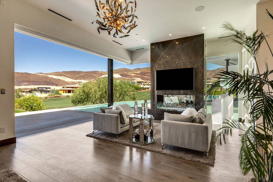 A sitting area with fireplace opens to the pool area. (Ivan Sher Group)