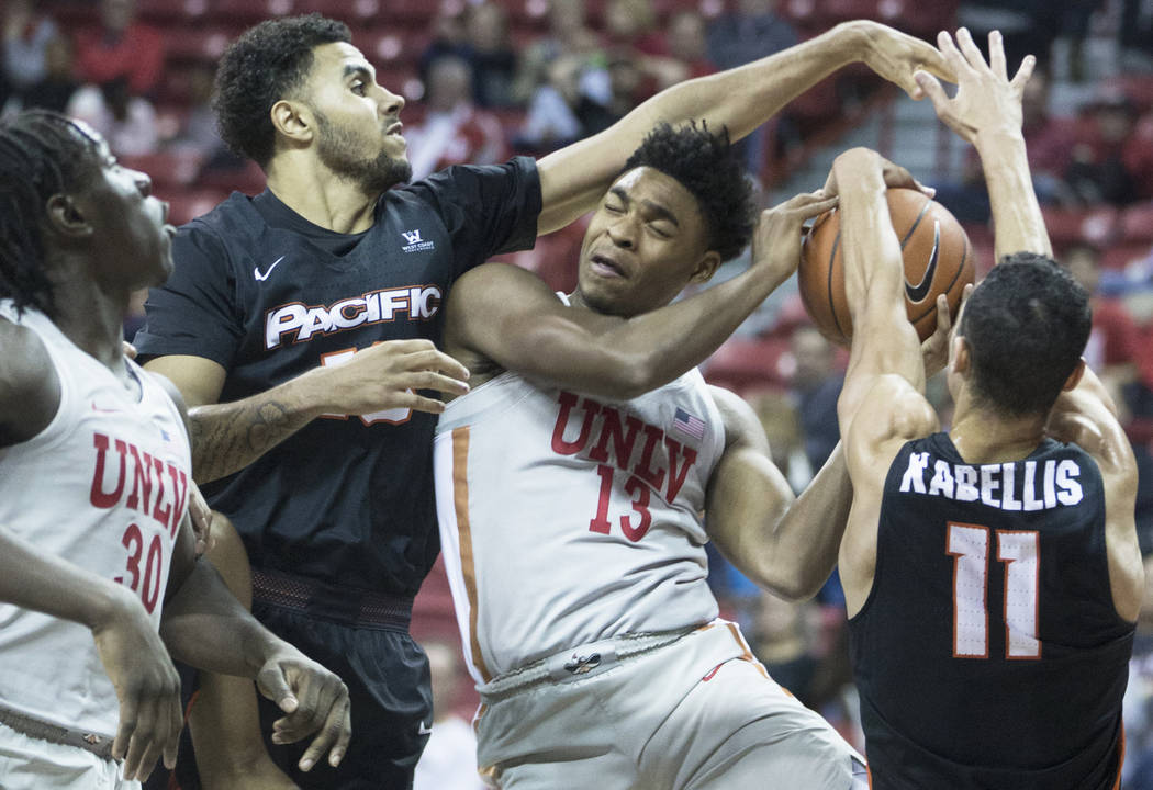 UNLV freshman guard Bryce Hamilton (13) collides with Pacific sophomore forward Jeremiah Bailey (13) and guard Khy Kabellis (11) on the way to the rim in the second half on Tuesday, Nov. 20, 2018, ...