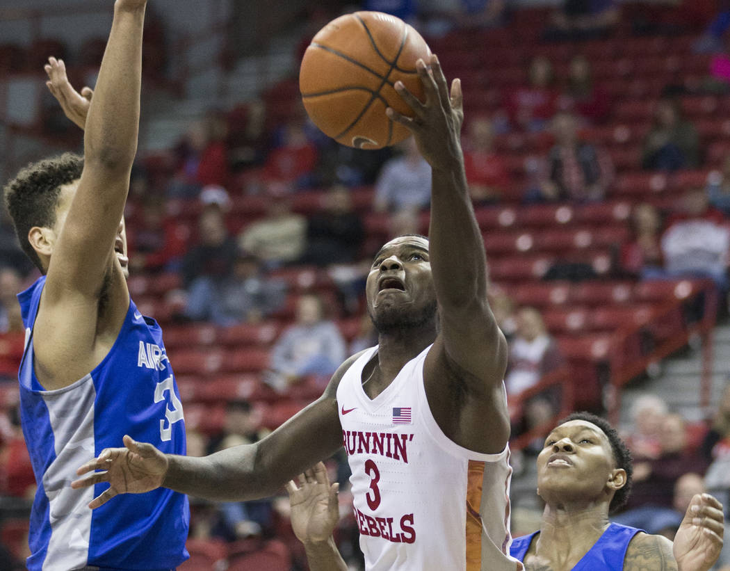 UNLV sophomore guard Amauri Hardy (3) drives baseline past Air Force junior forward Ryan Swan (34) and guard Zach Couper (2) in the second half on Tuesday, Feb. 12, 2019, at the Thomas & Mack ...