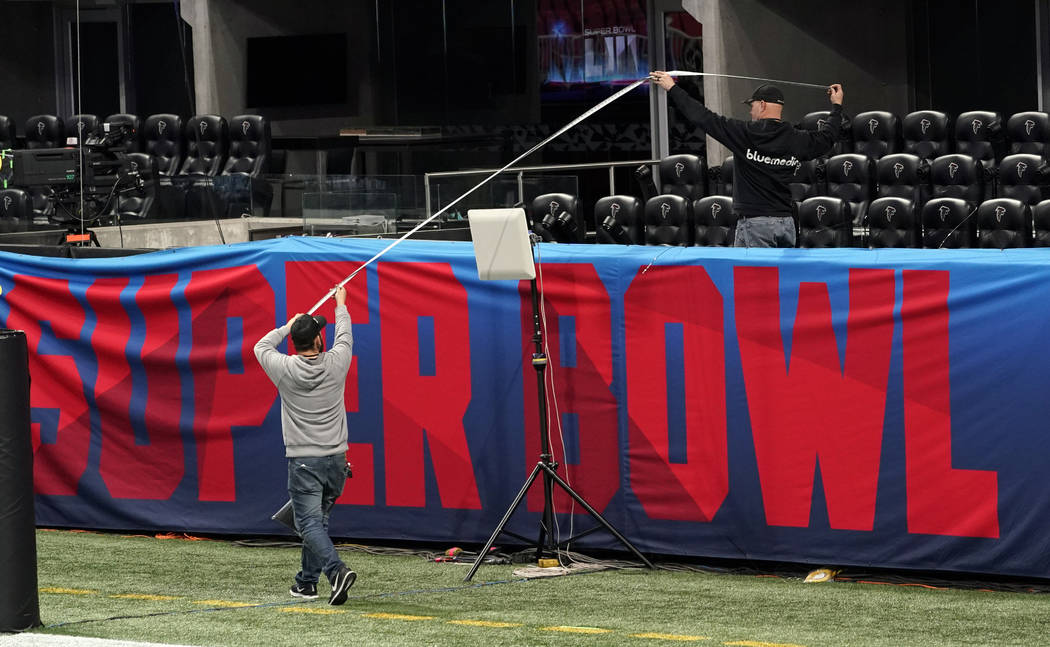 Workers use a tape measure as they hang a sign inside Mercedes-Benz Stadium for the NFL Super Bowl 53 football game Tuesday, Jan. 29, 2019, in Atlanta. (AP Photo/David J. Phillip)