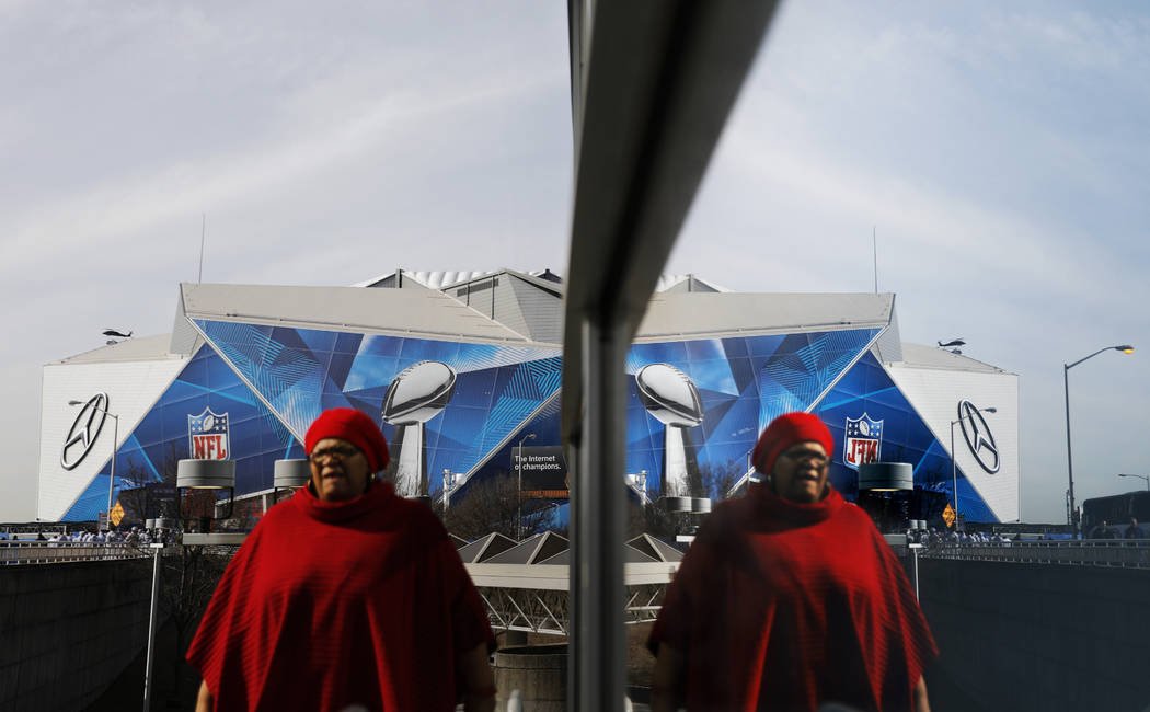 Mercedes-Benz Stadium is reflected in a window ahead of Sunday's NFL Super Bowl 53 football game between the Los Angeles Rams and New England Patriots in Atlanta, Friday, Feb. 1, 2019. (AP Photo/D ...
