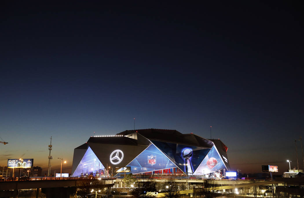 The sun sets behind Mercedes-Benz Stadium ahead of Sunday's NFL Super Bowl 53 football game between the Los Angeles Rams and New England Patriots in Atlanta, Wednesday, Jan. 30, 2019. (AP Photo/Da ...