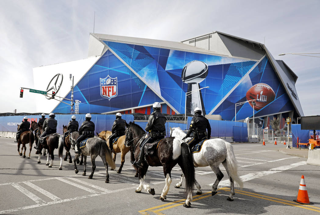 Police on horseback patrol past Mercedes-Benz Stadium ahead of Sunday's NFL Super Bowl 53 football game between the Los Angeles Rams and New England Patriots in Atlanta, Wednesday, Jan. 30, 2019. ...