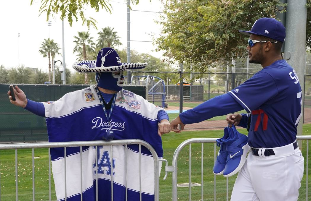 Los Angeles Dodgers' Dennis Santana is greeted by fan Carlos Morales at a spring training baseball workout Wednesday, Feb. 13, 2019, in Glendale, Ariz. (AP Photo/Morry Gash)