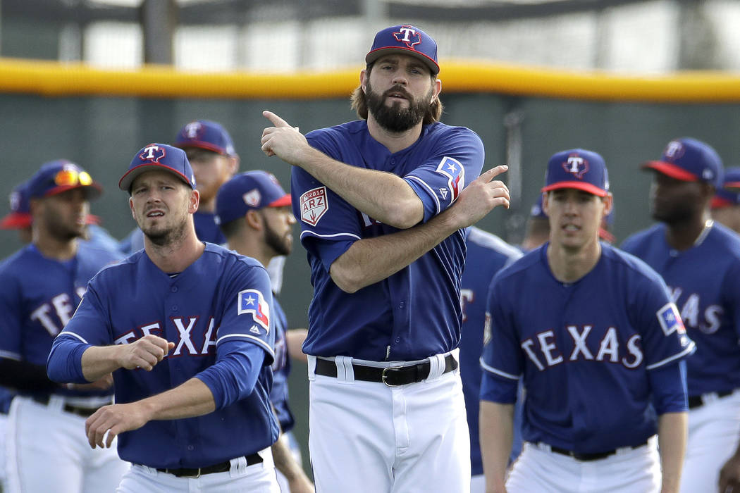 Texas Rangers pitcher Jason Hammel, front, warms up with teammates during spring training baseball practice Friday, Feb. 15, 2019, in Surprise, Ariz. (AP Photo/Charlie Riedel)