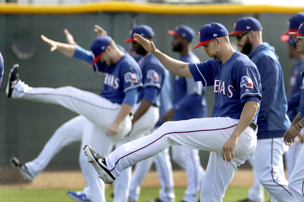 Texas Rangers pitcher Mike Minor, front, stretches with teammates during spring training baseball practice Friday, Feb. 15, 2019, in Surprise, Ariz. (AP Photo/Charlie Riedel)
