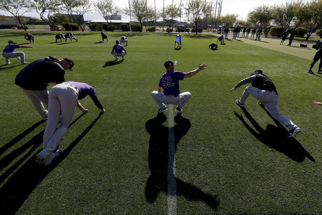 Members of the Colorado Rockies pitching staff warm up at their spring baseball training facility in Scottsdale, Ariz., Saturday, Feb. 16, 2019. (AP Photo/Chris Carlson)