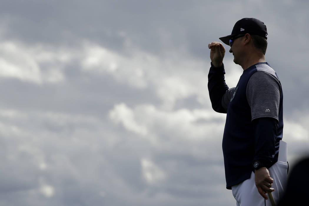 Seattle Mariners manager Scott Servais watches a drill during spring training baseball practice Saturday, Feb. 16, 2019, in Peoria, Ariz. (AP Photo/Charlie Riedel)