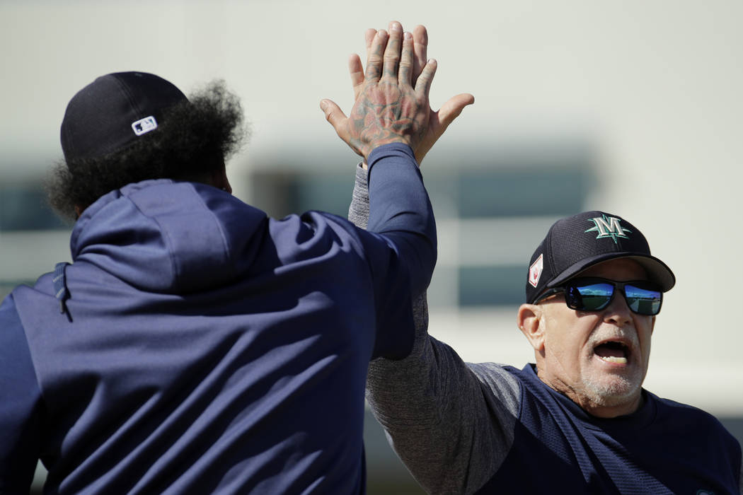 Seattle Mariners first base coach Perry Hill, right, high-fives pitcher Felix Hernandez during spring training baseball practice Saturday, Feb. 16, 2019, in Peoria, Ariz. (AP Photo/Charlie Riedel)