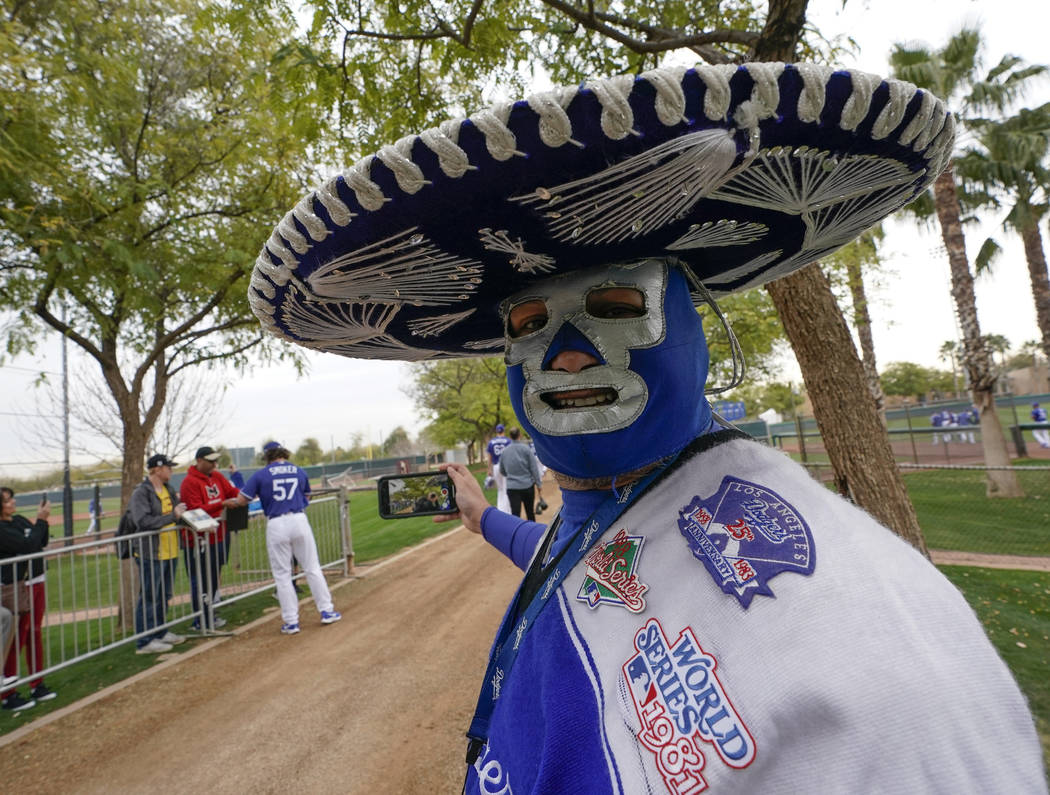 Los Angeles Dodgers' fan Carlos Morales greets players at a spring training baseball workout Wednesday, Feb. 13, 2019, in Glendale, Ariz. (AP Photo/Morry Gash)