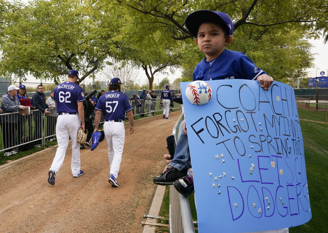 A Los Angeles Dodgers fan watches as players make their way to a spring training baseball workout Wednesday, Feb. 13, 2019, in Glendale, Ariz. (AP Photo/Morry Gash)