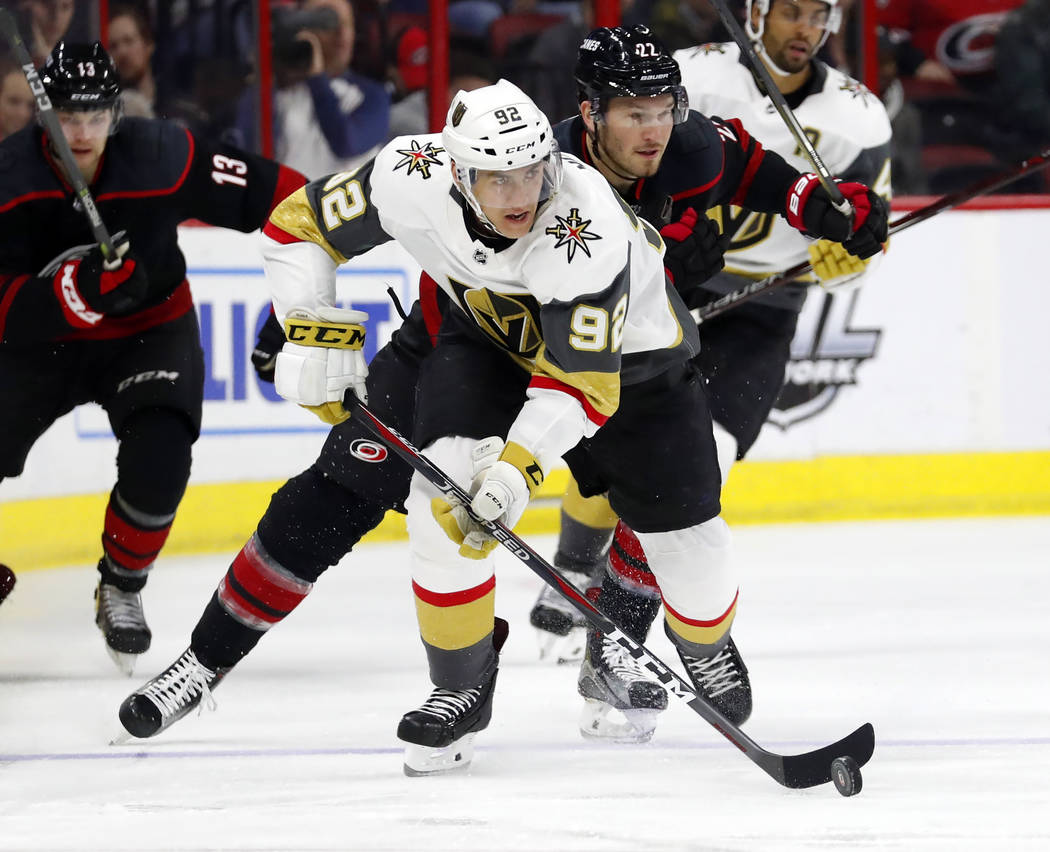 Vegas Golden Knights' Tomas Nosek (92) sakes with the puck after taking it from Carolina Hurricanes' Brett Pesce (22) during the first period of an NHL hockey game Friday, Feb. 1, 2019, in Raleigh ...