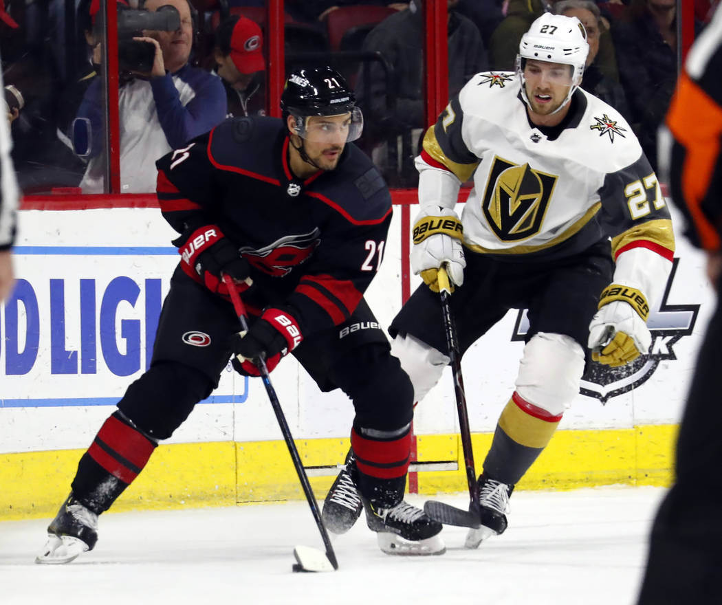 Carolina Hurricanes' Nino Niederreiter (21) looks to pass the puck while being defended by Vegas Golden Knights' Shea Theodore (27) during the third period of an NHL hockey game Friday, Feb. 1, 20 ...