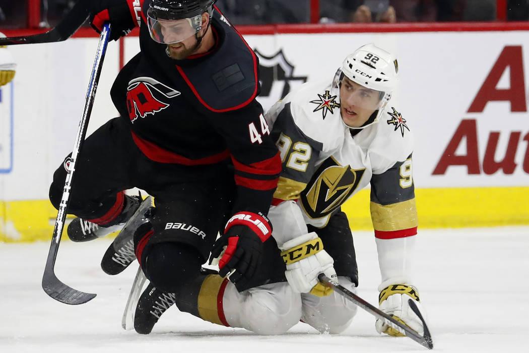 Carolina Hurricanes' Calvin de Haan (44) trips over Vegas Golden Knights' Tomas Nosek (92) during the third period of an NHL hockey game Friday, Feb. 1, 2019, in Raleigh, N.C. (AP Photo/Karl B DeB ...