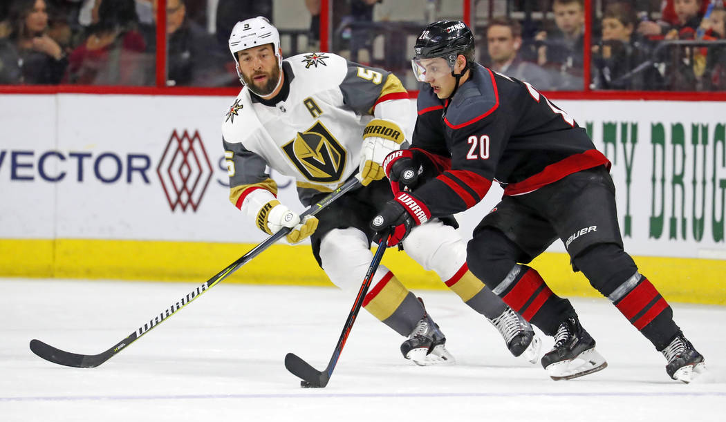 Carolina Hurricanes' Sebastian Aho (20) moves the puck against Vegas Golden Knights' Deryk Engelland (5) during the first period of an NHL hockey game Friday, Feb. 1, 2019, in Raleigh, N.C. (AP Ph ...
