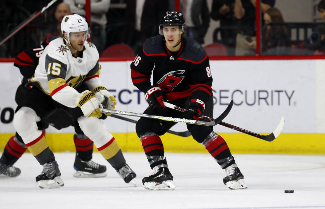 Carolina Hurricanes' Teuvo Teravainen (86) looks to pass the puck while being defended by Vegas Golden Knights' Jon Merrill (15) during the third period of an NHL hockey game Friday, Feb. 1, 2019, ...