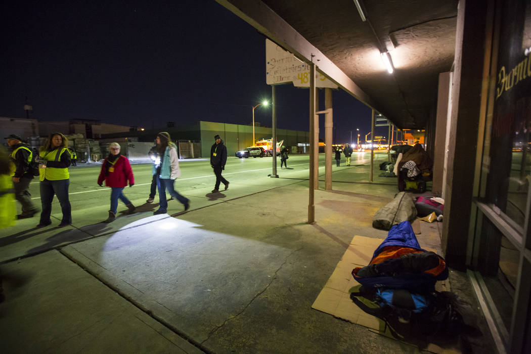 Homeless people sleep outside of businesses along Main Street as volunteers walk the area for the annual Southern Nevada Homeless Census goes on in Las Vegas on Tuesday, Jan. 22, 2019. (Chase Stev ...