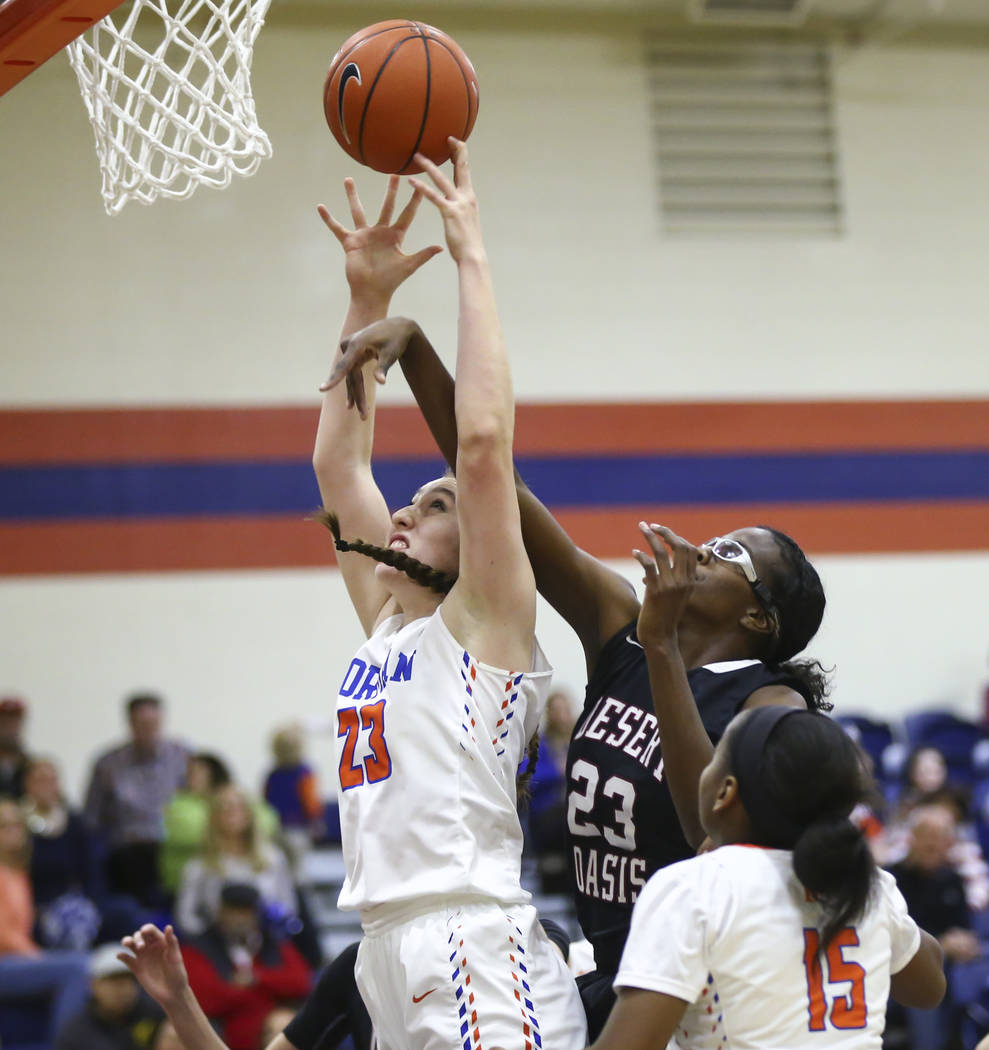 Bishop Gorman's Tierney Holcombe, left, shoots the ball under pressure from Desert Oasis' Desi-Rae Young during the first half of a basketball game at Bishop Gorman High School in Las Vegas on Fri ...