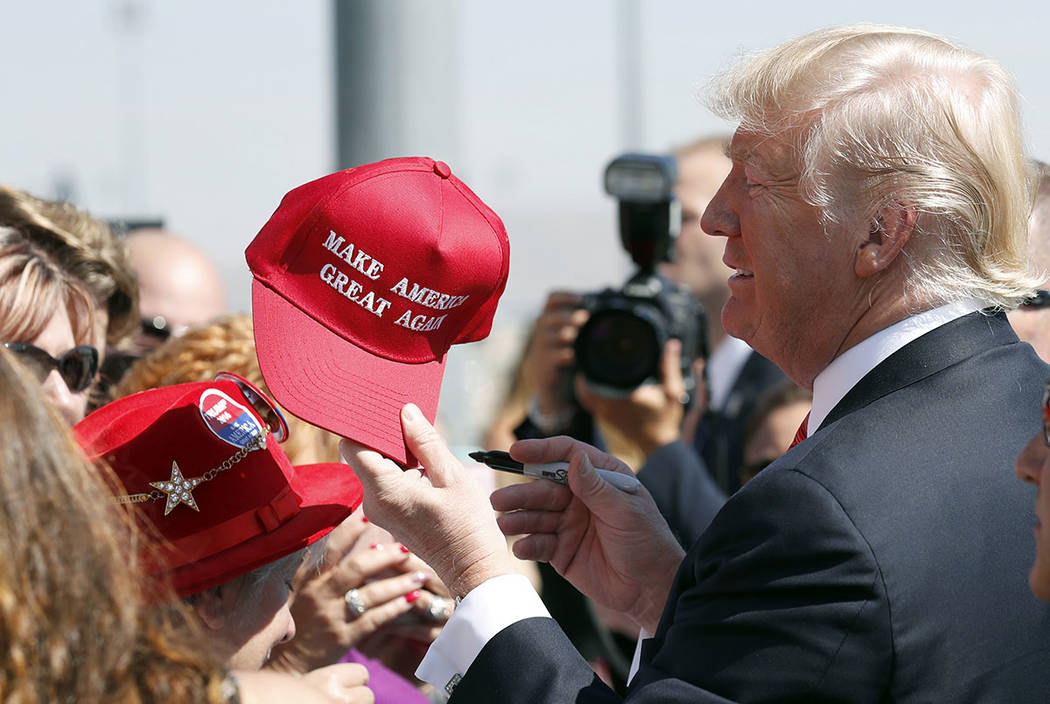 """President Donald Trump hands a signed """"Make America Great Again"""" hat back to a supporter in Reno in August 2017. (AP Photo/Alex Brandon, File)"""
