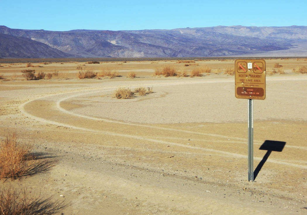 This undated photo shows vehicle tracks beyond a sign banning vehicles in the North Panamint dry lake area during the recent federal government shutdown in an area of Death Valley National Park, C ...
