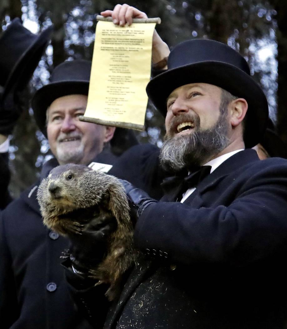 Groundhog Club co-handler Al Dereume, right, holds Punxsutawney Phil, the weather prognosticating groundhog, during the 133rd celebration of Groundhog Day on Gobbler's Knob in Punxsutawney, Pa. Sa ...
