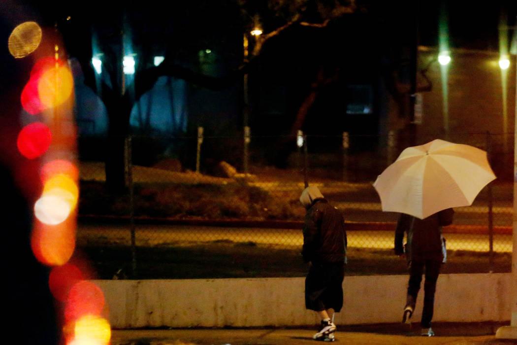 Pedestrians walk in the rain on Bonanza Road in Las Vegas, Saturday, Feb. 2, 2019. Chitose Suzuki Las Vegas Review-Journal @chitosephoto