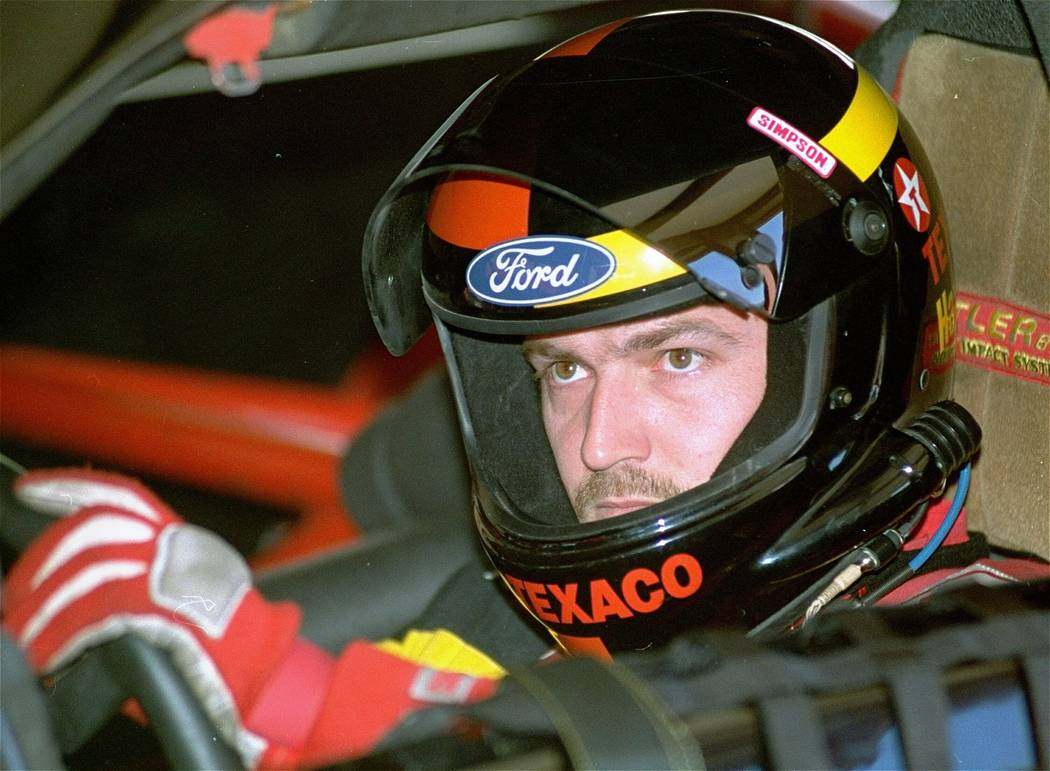 Driver Davey Allison sits in his car as it is checked after a practice run for the NASCAR auto race at Atlanta Motor Speedway in Hampton, Ga. on Nov. 13, 1992. Allison is being inducted into the ...