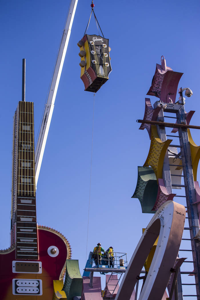 The headstock piece of the Hard Rock Cafe guitar sign is raised into the air as YESCO employees install the sign at the Neon Museum in Las Vegas on Friday, Feb. 1, 2019. (Chase Stevens/Las Vegas R ...
