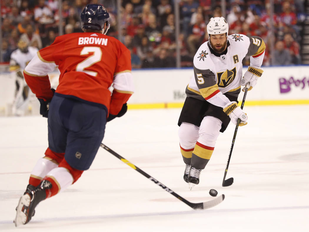 Vegas Golden Knights defenseman Deryk Engelland (5) takes the puck downice against Florida Panthers defenseman Josh Brown (2) during the first period of an NHL hockey game, Saturday, Feb. 2, 2019, ...