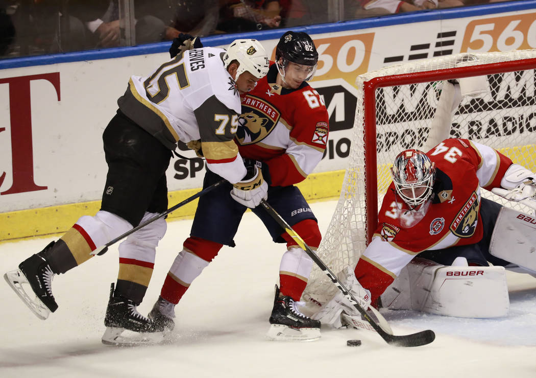Vegas Golden Knights right wing Ryan Reaves (75) attempts to shoot at Florida Panthers goaltender James Reimer (34) and center Denis Malgin (62) during the second period of an NHL hockey game, Sat ...