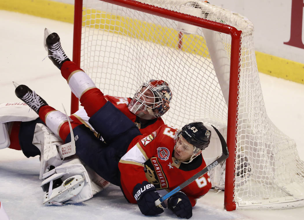 Florida Panthers right wing Evgenii Dadonov (63) falls atop goaltender James Reimer during the third period of an NHL hockey game against the Vegas Golden Knights, Saturday, Feb. 2, 2019 in Sunris ...